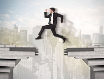 Homem de negócio energético que salta sobre uma ponte com diferença fotografia de stock royalty free