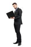 Homem de negócio ereto novo que trabalha em um portátil Fotografia de Stock Royalty Free