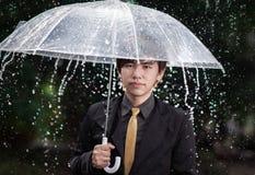 Homem de negócio esperto que guarda o guarda-chuva entre a chuva Fotos de Stock Royalty Free