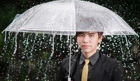 Homem de negócio esperto que guarda o guarda-chuva entre a chuva Foto de Stock