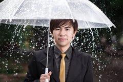 Homem de negócio esperto que guarda o guarda-chuva entre a chuva Fotos de Stock