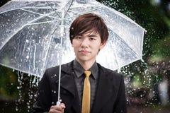 Homem de negócio esperto que guarda o guarda-chuva entre a chuva Imagens de Stock Royalty Free