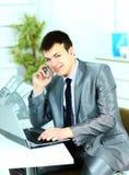 Homem de negócio esperto que usa o portátil no escritório moderno Fotos de Stock