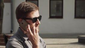 Homem de negócio europeu nos óculos de sol que fala no smartphone na rua urbana video estoque