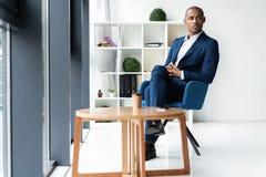 Homem de negócio executivo afro-americano alegre considerável no escritório do espaço de trabalho fotografia de stock