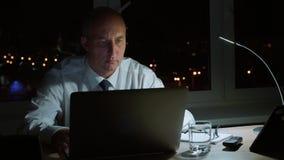 Homem de negócio executivo que trabalha pelo caderno enfim que nivela no escritório escuro vídeos de arquivo
