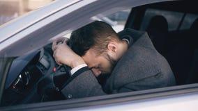 Homem de negócio farpado novo que senta-se no carro muito virado e forçado após a falha dura e que move-se no engarrafamento fotografia de stock royalty free