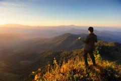 Homem de negócio feliz na montanha e no por do sol quando sucesso foto de stock