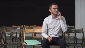 Homem de negócio feliz novo que fala em um telefone celular vídeos de arquivo