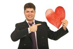 Homem de negócio feliz que aponta ao coração Fotografia de Stock Royalty Free