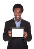 Homem de negócio feliz que guarda a tabuleta de Digitas fotografia de stock royalty free