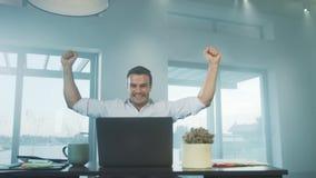 Homem de negócio feliz que obtém a boa notícia no laptop no local de trabalho remoto vídeos de arquivo