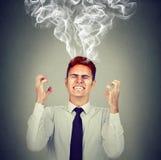 Homem de negócio forçado que tem o vapor da dor de cabeça que vem acima foto de stock