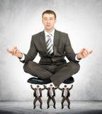 Homem de negócio gigante que senta-se em homens pequenos Imagem de Stock