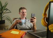 Homem de negócio independente atrativo e bem sucedido novo que usa o telefone celular que envia o texto que trabalha no hispter m imagem de stock royalty free