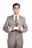 Homem de negócio indiano que prende um cartão conhecido. fotografia de stock