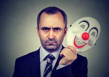 Homem de negócio irritado que descola a máscara feliz do palhaço imagens de stock royalty free
