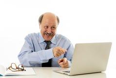 Homem de negócio maduro satisfeito em seu 60s que trabalha no portátil seguro do sucesso fotografia de stock