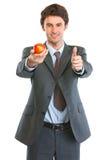 Homem de negócio moderno que mostra a maçã e os polegares acima Fotografia de Stock Royalty Free