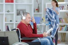 Homem de negócio na cadeira de rodas com o assistente no fundo fotografia de stock
