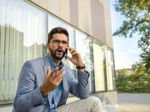 Homem de negócio na conversação má no smartphone fotografia de stock royalty free
