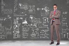 Homem de negócio na frente de uma parede com planos grandes fotografia de stock