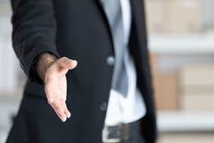 Homem de negócio na mão aberta do terno preto pronta para agitar as mãos, paridade foto de stock