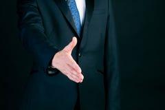 Homem de negócio no aperto de mão de oferecimento do terno Fotografia de Stock Royalty Free