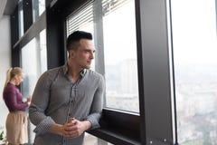 Homem de negócio no escritório que olha através da janela Fotografia de Stock Royalty Free