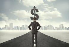 Homem de negócio no título da estrada para um sinal de dólar Fotos de Stock Royalty Free