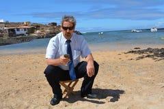 Homem de negócio no terno na praia que chama por mobil Imagens de Stock Royalty Free