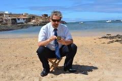 Homem de negócio no terno na praia que chama por mobil Fotos de Stock
