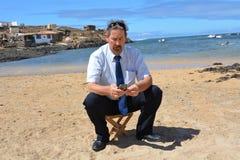 Homem de negócio no terno na praia que chama por mobil Fotografia de Stock