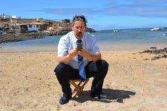 Homem de negócio no terno na praia que chama por mobil Imagem de Stock
