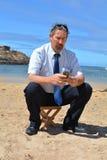 Homem de negócio no terno na praia que chama por mobil Imagens de Stock