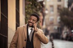 Homem de negócio novo atrativo feliz em seu telefone esperto ao andar no sorriso da cidade foto de stock royalty free