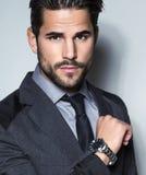 Homem de negócio novo considerável no terno no fundo cinzento Imagens de Stock Royalty Free