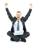Homem de negócio novo feliz que trabalha em um portátil fotografia de stock