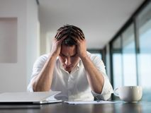 Homem de negócio novo frustrante que trabalha no laptop em casa Fotografia de Stock Royalty Free