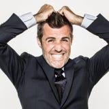 Homem de negócio novo irritado que retira seu cabelo para a neutralização imagem de stock