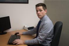 Homem de negócio novo na mesa no escritório Foto de Stock Royalty Free