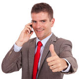 Homem de negócio novo no gesto da aprovação do telefone Imagem de Stock