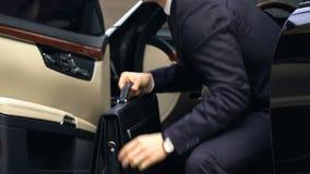 Homem de negócio novo no terno com sair da pasta do carro preto caro vídeos de arquivo