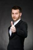 Homem de negócio novo no terno preto com polegares acima Imagens de Stock