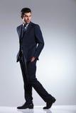 Homem de negócio novo que anda no fundo cinzento do estúdio Imagens de Stock