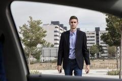Homem de negócio novo que anda para o carro Fotografia de Stock