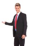 Homem de negócio novo que apresenta algo Fotos de Stock