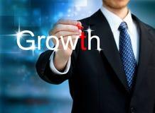 Homem de negócio novo que escreve o crescimento da palavra imagem de stock