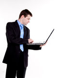 Homem de negócio novo que está com portátil foto de stock