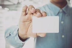 Homem de negócio novo que guarda o cartão branco no escritório moderno Fotos de Stock